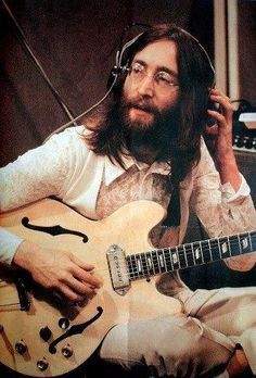 John Lennon w/ith hollow body blond Epiphone Casino electric guitar, in the…