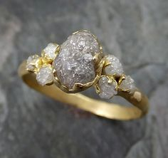 This diamond ring is a size 6 3/4 and can be sized. I created a rustic texture in the solid 18k gold with 2mm diamonds on the gold on each side. The main diamon