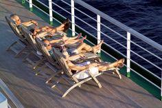 Guests relaxing on deck on board Queen Elizabeth 2.