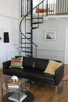 13 Stair Design Ideas For Small Spaces // The thin spiral staircase leading up to the bedroom of this house compliments the other black elements in the home and takes up very little space.