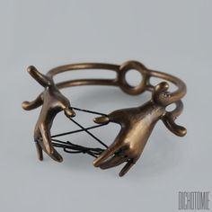 "Invoke your will with The Conjuror Bangle. Designed for a dear friend, this piece features a set of hands playing the game of cat's cradle. Each hand is supported by ornamental filgree and a doublet band meeting in the center. Cast in bronze with an antique finish, this is a statement piece in both scale and weight. Dimensions - 3 1/4"" x 3 3/8"" x 1 3/4""  
