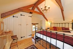 Throughout the barn are exposed beams and the galleried bedroom nestles under the eaves.