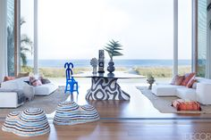 Behun designed the loggia's table, which has a base of hand-cut ceramic mosaic tiles and a Macassar ebony top; the Living Divani sofas are upholstered in a Holly Hunt linen, the wicker stools are by IKEA, the rope stool and blue chair are by Christian Astuguevieille, and the custom rugs are made from African raffia ceremonial cloths.   - ELLEDecor.com