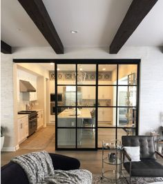 Separate your kitchen and living room area with clear glass room dividers, shown here in a black aluminum frame. Living Room Sliding Doors, Kitchen Sliding Doors, Sliding Door Room Dividers, Living Room Partition, Living Room Divider, Living Room Kitchen Partition Designs, Modern Room Dividers, Closet Doors, Glass Room Divider