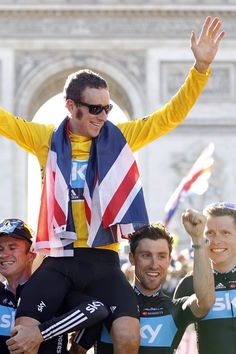 Sky Procycling rider and leader's yellow jersey Bradley Wiggins of Britain wears a British national flag as he celebrates with team mates his overall victory in front the Arc de Triomphe in Paris