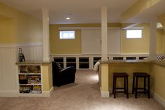 Basement remodel photos, interesting bar idea around poles -- I like the storage on one side and the bar option on the other