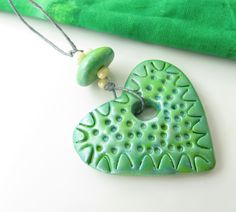 Polymer clay heart is approx. 40x40mm with large hole for… http://artisancomponentmarketplace.com/metapolies/store/products/green-textured-heart-pendant-and-bead-pc14-090acm/