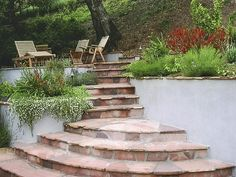 This flagstone stairway begins with wide, circular steps which narrow as they approach the lounging area at the top. Draping flowers spill over the edges of raised planters along the pathway for a stunning, all-natural look. Design by Joan Grabel Small Outdoor Spaces, Outdoor Rooms, Outdoor Living, Raised Patio, Outdoor Steps, Hillside Landscaping, Garden Steps, Garden Pictures, Back Gardens