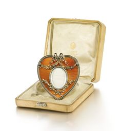 An Imperial Fabergé gold-mounted enamel frame, workmaster Victor Aarne, St Petersburg, 1899. Heart-shaped, the surface of translucent orange enamel over banded sunburst engine-turning within a gadrooned border, the oval aperture with seed pearl bezel within ribbon-hung vari-coloured gold floral boughs. Purchased by Empress Alexandra Feodorovna on 1 May 1899 for 100 roubles.