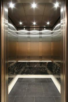 Elevator interior with black stone base