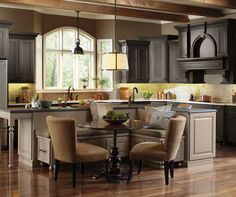 Enjoy a feast of creative ideas. Ornate mouldings draw the eye up, while architectural detail on the large kitchen island creates interest at the floor level. Combining styles with complementary flat and raised panels and contrasting finishes create a space that is beautifully unique.