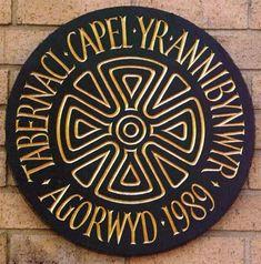 Circular plaque design with gold text.