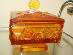 "VINTAGE Fenton Art Glass Amber HONEYCOMB & BEE LIDDED HONEY DISH.Was designed by a Illinois Beekeeper made by Fenton for him, sold in the January 1965 Fenton catalog 5""H (to finial x 4.5""square (3""H without lid). Amber Glass, Bee Keeping, Honeycomb, Illinois, Glass Art, Pots, Catalog, January, Decorative Boxes"