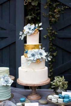 Pastel de boda de bordes rectos con metalizado en dorado y acentos de flores en azul serenity. Acompáñala con macaroons al tono.