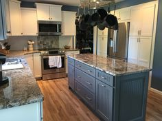 White cabinets set off by Leisure Blue Sherwin Williams paint, with a gray island, Diamond Wave granite countertops, Kardean flooring, Bosch refrigerator, microwave  and stove. Very cozy and comfortable. I love it!