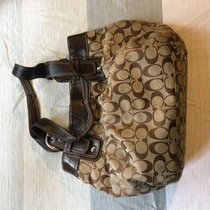 Make me an offer! Brown and tan coach bag. Used and slightly worn. About 14 inches wide and 10 inches tall. Coach Bags Totes