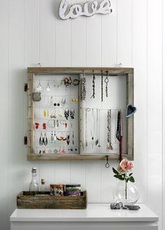 En gammel vinduskarm i tre er hengt på veggen, og fungerer nå som smykkestativ ved hjelp av spiker og vaiere. Kommoden under er også lekkert dekorert med steiner, gamle bokser og flasker og en trekasse.