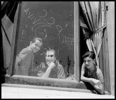 by Gerda Taro Three men in the window of the Hotel Colón, headquarters of the PSUC (United Socialist Party of Catalonia), Barcelona, August 1936.