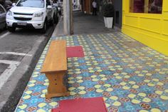 calçada diferenciada, banco e loja amarela