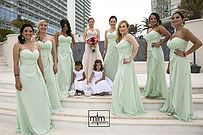 Bridal party surrounding beautiful Bride and flower girl at this gorgeous Sandos Cancun wedding celebration!    MTM Photography in Mayan Riviera Wedding Photographer. Wedding Photographer photos in Cancun, Playa del Carmen, Puerto Morelos, Puerto Aventuras and Tulum. www.MomentsThatMatterPhotography.com