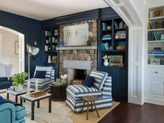 Blue cottage den features a wall of navy built-in shelves and cabinets flanking a rustic stone ...