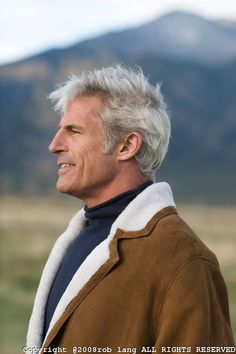 handsome man with gray hair looking off while standing in a field in Taos, New…