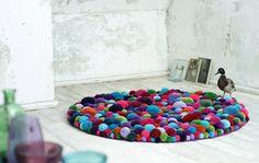 DIY ~ fun pom pom carpet {cut carpet gripper/carpet pad in a circular shape and adhere pom poms}