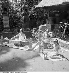 Twee meisjes zitten in een kampong op Bali aan een weefgetouw te werken vanwege een filmopname, gemaakt door Jaap Zindler, Indonesië (1947)