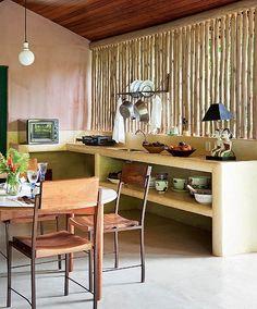 A cozinha simples de casa de praia tem bancada de cimento queimado. A moradia fica nos fundos da Marcenaria Trancoso, na Bahia
