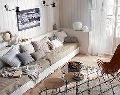 """Un salon aux allures de maison de vacances… Une accueillante banquette """"ras-du-sol"""" construite sur mesure, agrémentée de coussins, d'un tapis style berbère et de tables plateaux. Dans une ambiance de couleurs minérales, l'ethnique, c'est chic!"""