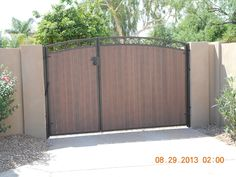 Beautiful RV gate in Phoenix custom designed with a slight arch and iron c-scrolls