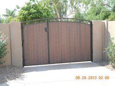 Beautiful RV gate in Phoenix custom designed with a slight arch and iron c-scrolls