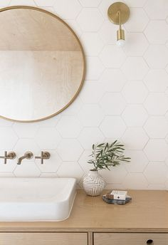 Gorgeous white honeycomb tile in the bathroom with a round mirror and brass fixtures
