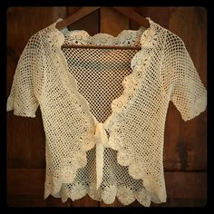 Beautiful crochet shrug Cream color shrug in a beautiful crochet pattern. Single front ribbon tie closure. Unsure of designer (no tags), but to the best of my recollection, I think it is from White House Black Market. White House Black Market Sweaters Shrugs & Ponchos