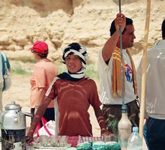 Little boy offers water and tea at the desert,Tunis