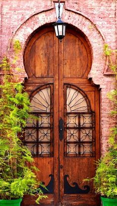 Spanish door surrounded by bricks and plants in Málaga, Andalusia, Spain. - photo by Maria Rojas