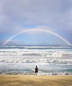 Image: A surfer takes a break from the waves to enjoy a rainbow from the beach. (© Ed Freeman/Getty Images)