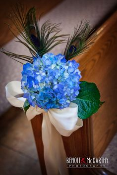 blue hydrangea with peacock feathers aisle decoration