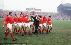 Manager Matt Busby holds the League Championship trophy aloft with his players at Old Trafford. Left-right: Denis Law, Bill Foulkes, John Aston, Shay Brennan, David Sadler, Bobby Charlton, Alex Stepney, Busby, Jimmy Ryan, Tony Dunne, Pat Crerand, George Best