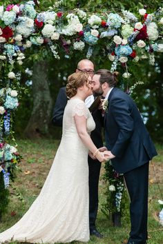The bride + groom share their first kiss under a floral arbor{Corey Cagle Photography}