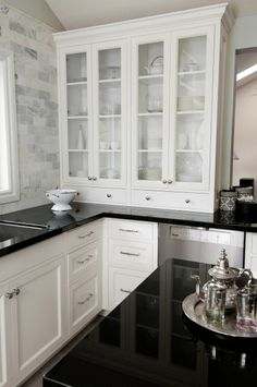 KITCHEN. white cabinetry. glass front up high... solid below.. black granite countertops. carrera marble subway tile backsplash.
