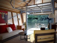 Interior of tiny house, looking out at the lake. Cool garage door and fantastic plan for anyone on a lake. | Tiny Homes