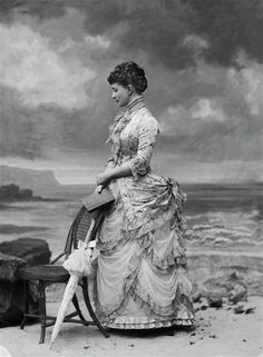 Bustled woman with a parasol and a seaside backdrop painting