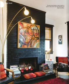 painted black fireplace, vintage light, teak chairs, stacks of books