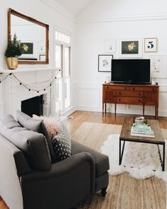 modern farmhouse LR ... mix new and antique furniture, comfy couch and chair, wood floor, painted brick fireplace, antique sideboard as TV stand