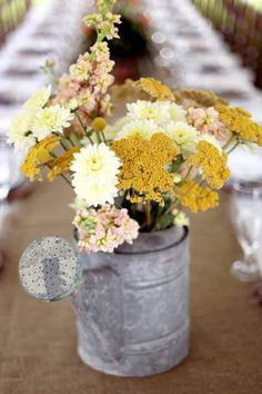The couple chose unusual containers for their tablcentres including antique teapots and old watering cans. The flowers used included white ranunculus and lisianthus, yellow freesias, mini carnations, asters, yellow yarrow, Queen Anne's lace, brown fern curls and salal tips.
