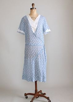 Vintage 1920s Blue and White Polka Dot Cotton Day/ House Dress: Lightweight, slightly sheer cotton with a blue and white polka dot print and white organdy trim.  Iconic 20s style with a straight silhouette and drop waist.  There is pleating on one side of the skirt.  The belt is stitched to the dress to be buckled at the side