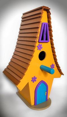 Whimsical style birdhouse, handmade from birch plywood and solid beech on the roof. Painted in yellow and brown, solidly constructed, has a hinged base so you can clean the inside when required and measures: 8 deep, 11 wide, 18 tall You can personalise the house with a little swing sign