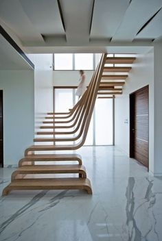 Beautifully Sloping Wooden Staircase Creates a Sense of Flow in the Home Idea for the wave la vague, wave themed staircase