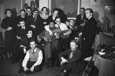 Émile Savitry - Alejo Carpentier, cuban writter, at home in Montparnasse in Paris 1936-1939 with friends such as Joan Miró, Joseph Reinhardt standing with a glass behind him, Stéphane Grappelli playing piano